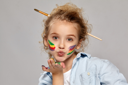Beautiful little girl with a painted hands and cheeks is posing on a gray background.