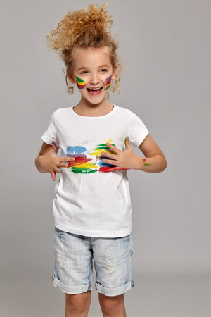 Beautiful little girl with a painted hands and cheeks is posing on a gray