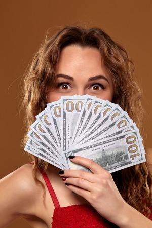 Image of lucky happy woman with brown long hair with fan of 100 dollar bills, lots of cash money, over brown