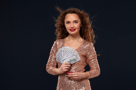 Image of lucky happy woman with brown long hair with fan of 100 dollar bills, lots of cash money, over black