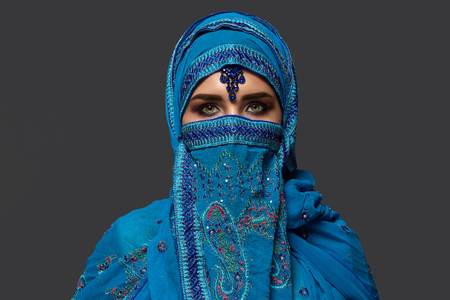 Studio shot of a young beautiful woman wearing the blue hijab decorated with sequins and jewelry. Arabic style. Standard-Bild
