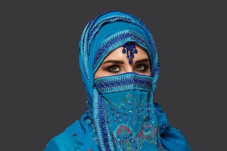 Studioaufnahme einer jungen schönen Frau, die den blauen Hijab trägt, der mit Pailletten und Schmuck verziert ist. Arabischer Stil. Standard-Bild