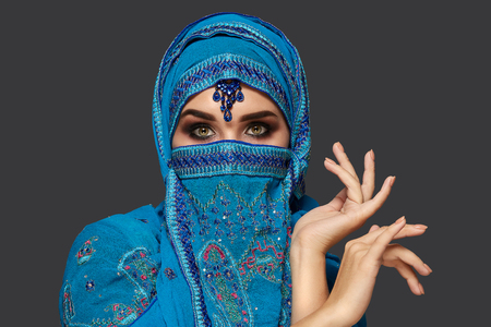 Studio shot of a young beautiful woman wearing the blue hijab decorated with sequins and jewelry. Arabic style. 版權商用圖片