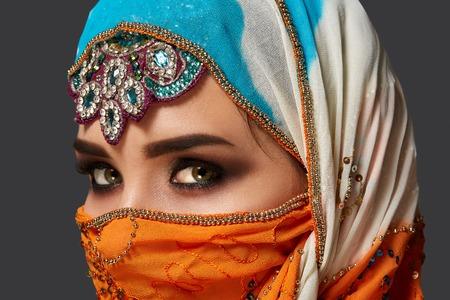 Studio ujęcia uroczej kobiety w kolorowym hidżabie ozdobionym cekinami i biżuterią. Styl arabski.
