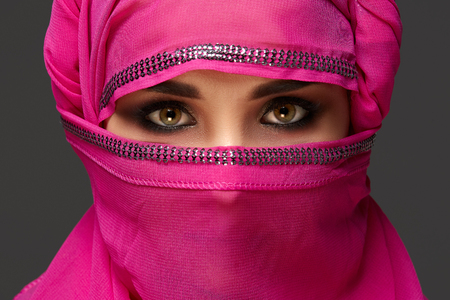 Close-up shot of a young charming woman wearing the pink hijab decorated with sequins. Arabic style. Standard-Bild