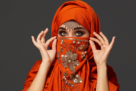 Studio shot of a young charming woman wearing the terracotta hijab decorated with sequins and jewelry. Arabic style.