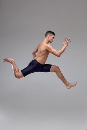 Photo of a handsome man ballet dancer, dressed in a black shorts, making a dance element against a gray background in studio. 写真素材 - 122606809