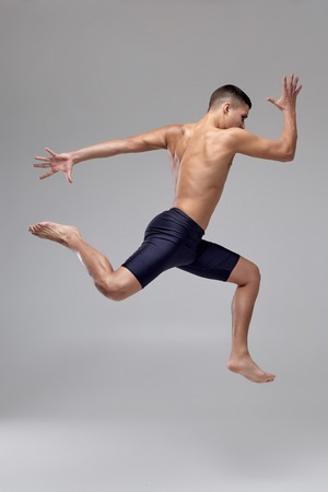 Photo of a handsome man ballet dancer, dressed in a black shorts, making a dance element against a gray background in studio.