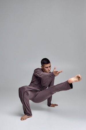 Photo of an athletic man ballet dancer dressed in a gray tracksuit, making a dance element against a gray background in studio. 写真素材 - 122607226