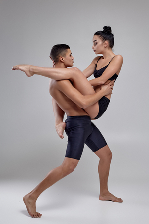 The couple of a young modern ballet dancers in black suits are posing over a gray studio background. 版權商用圖片