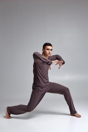 Foto de un bailarín de ballet atlético vestido con un chándal gris, haciendo un elemento de danza sobre un fondo gris en el estudio.