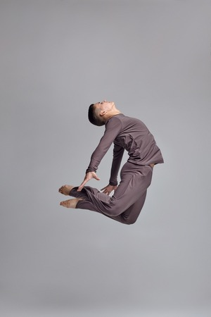 Photo of an athletic man ballet dancer dressed in a gray tracksuit, making a dance element against a gray background in studio. 写真素材 - 122607290