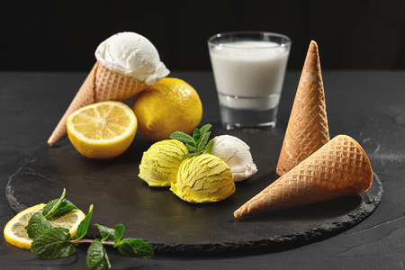 Tasty creamy and lemon ice cream decorated with mint served on a stone slate over a black background. Stockfoto