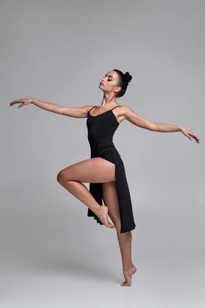 Tanzende Ballerina in einem schwarzen Kleid. Zeitgenössische anmutige Leistung auf grauem Hintergrund.