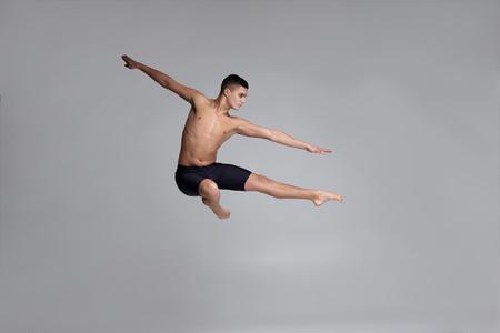 Foto van een knappe man balletdanser, gekleed in een zwarte korte broek, een danselement makend tegen een grijze achtergrond in de studio. Stockfoto