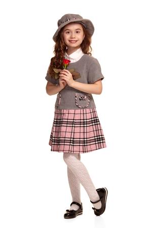 Aufnahme in voller Länge von einem schönen kleinen Kind mit einem langen, lockigen Haar, das isoliert auf weißem Hintergrund posiert.