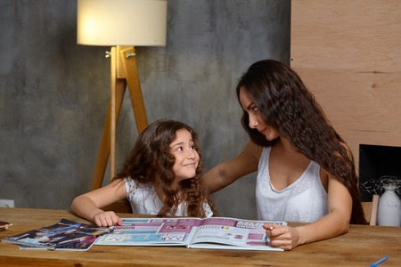 Portrait of a mother helping her small sweet and cute daughter to make her homework indoors. Happy family.