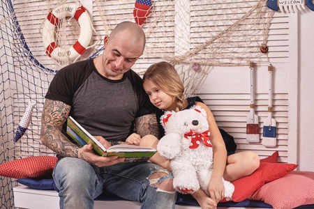 Handsome tattoed man is spending time with his little cute daughter. Reading fairytales while daughter is sitting nearby. Happy family.
