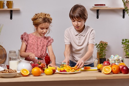 Cute kids are cooking together in a kitchen against a white wall with shelves on it.