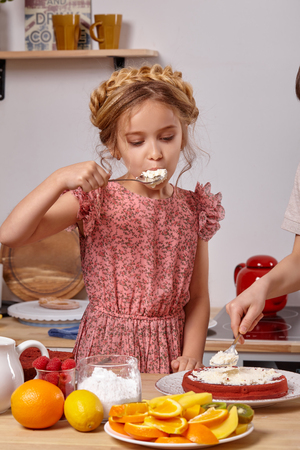 Little girl is making a homemade cake with an easy recipe at kitchen against a white wall with shelves on it.