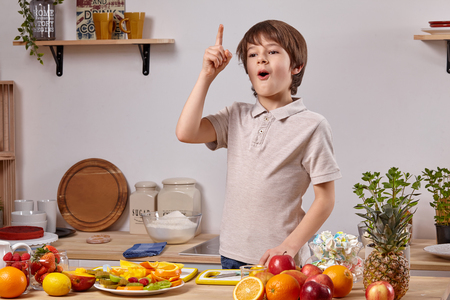 Cute little boy with brown hair is cooking at a kitchen against a white wall with shelves on it. Stok Fotoğraf