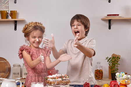 Little friends are making a cake together at a kitchen against a white wall with shelves on it.