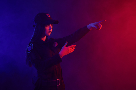 Redheaded female police officer is posing for the camera against a black background with red and blue backlighting.