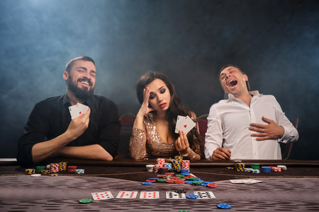 Group of a young rich friends are playing poker in casino. Stok Fotoğraf
