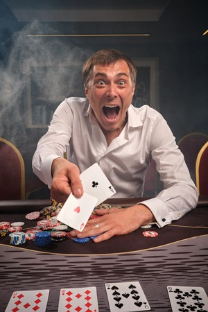 Handsome emotional man is playing poker sitting at the table in casino. 写真素材 - 124371779