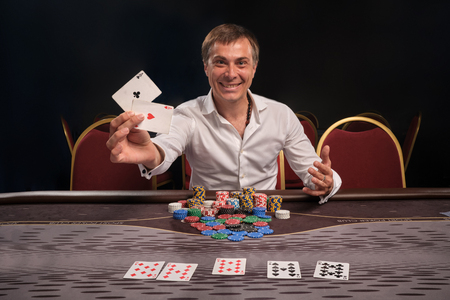 Handsome emotional man is playing poker sitting at the table in casino. 写真素材 - 124371527