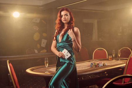 Young beautiful woman is posing against a poker table in luxury casino. Stok Fotoğraf