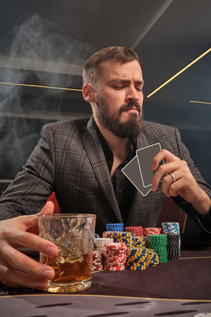 Handsome bearded man is playing poker sitting at the table in casino.
