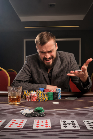 Handsome bearded man is playing poker sitting at the table in casino. 写真素材 - 124371383