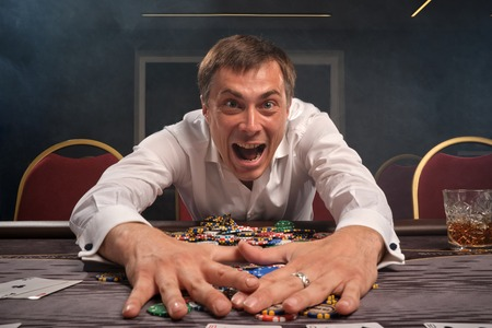 Handsome emotional man is playing poker sitting at the table in casino. Imagens