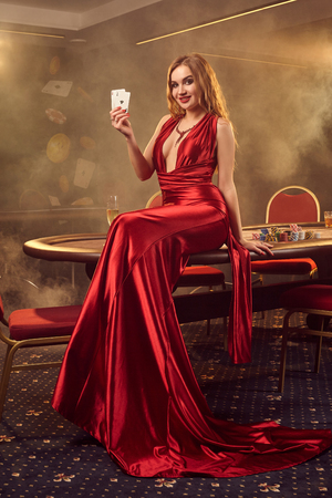 Young beautiful woman is posing against a poker table in luxury casino. Imagens
