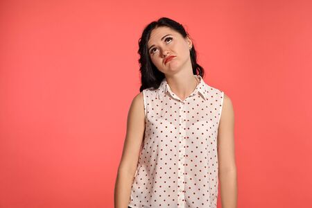 Studio shot of a beautiful girl teenager posing over a pink background.