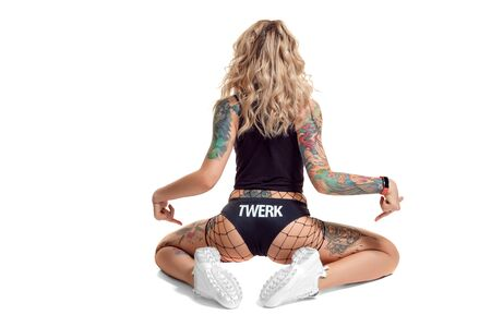Sexy blond twerk woman with tattoed body and long curly hair is posing in studio.