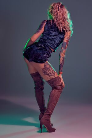 Attractive young blonde girl in blue velour booty shorts and maroon suede high boots posing on camera in studio