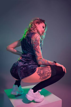 Young fitness blonde woman wearing blue velour booty shorts posing on camera, making squats on top of big cube