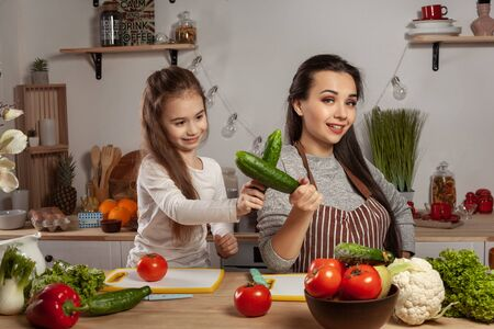 Mother and her daughter are making a vegetable salad and having fun at the kitchen. Imagens