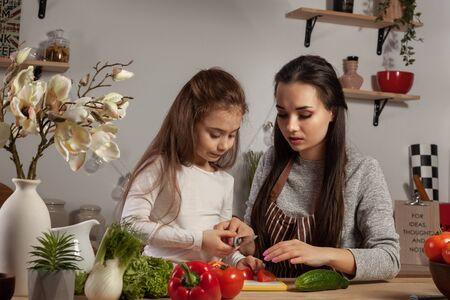 Madre e figlia stanno preparando un'insalata di verdure e si divertono in cucina.