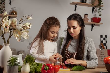Mother and her daughter are making a vegetable salad and having fun at the kitchen.