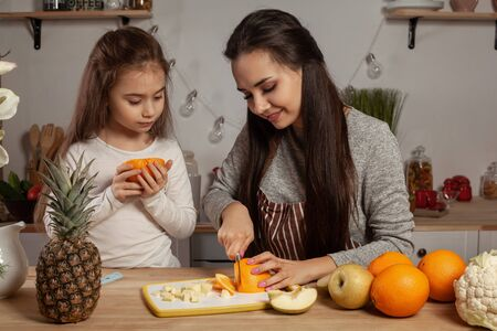 Mother and her daughter are doing a fruit cutting and having fun at the kitchen. Reklamní fotografie