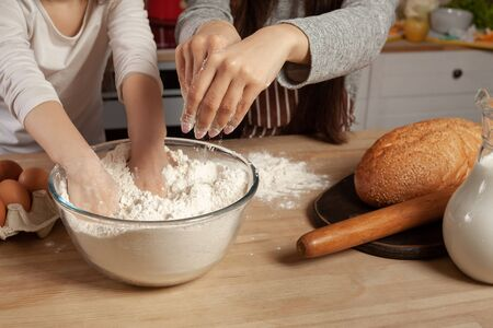 Mother and her daughter are baking a bread and having fun at the kitchen.