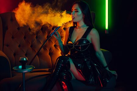 Sexy brunette model is smoking a hookah exhaling a smoke at a luxury night club. Фото со стока