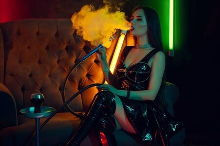 Modelo morena sexy está fumando una pipa de agua exhalando un humo en un club nocturno de lujo. Foto de archivo