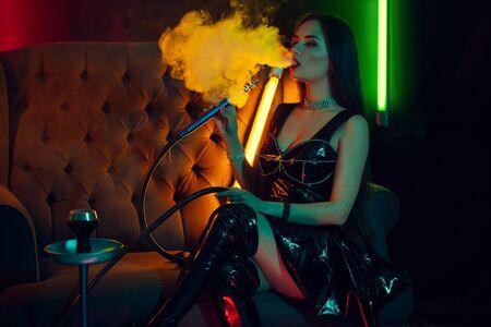 Sexy brunette model rookt een waterpijp die een rook uitademt in een luxe nachtclub. Stockfoto