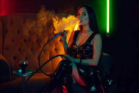 Sexy brunette model is smoking a hookah exhaling a smoke at a luxury night club. Stock Photo