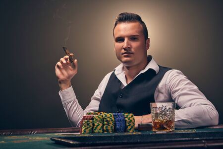 Wealthy man is smoking a cigar and playing poker with an excitement at a casino on black background.