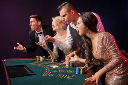 Group of a stylish rich friends are playing poker at casino.